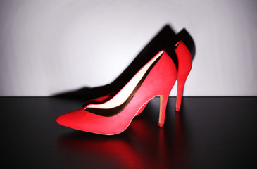 Pair of woman's red shoes on floor on light wall background