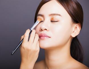 Make up artist applying  color eyeshadow on model's eye