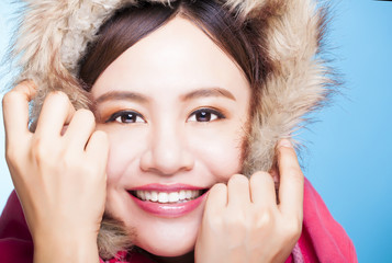 smiling asian girl with winter wear sweater.isolated on blue bac