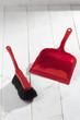 canvas print picture - Roter Handfeger und Schaufel auf weissem Holzuntergrund, Studio