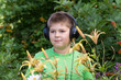 boy listening to music with headphones in  park