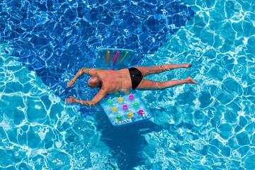 man relaxing on swimming-pool