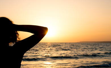 Silhouette of woman relaxing against sunset.