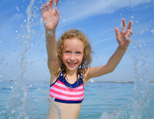 Happy child playing in the sea.