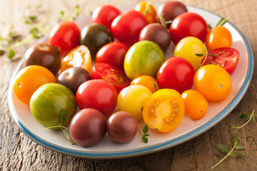 colorful tomatoes in plate on wooden background