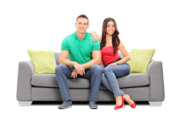 Young couple posing seated on a modern sofa