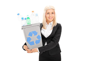 Young businesswoman holding a recycle bin