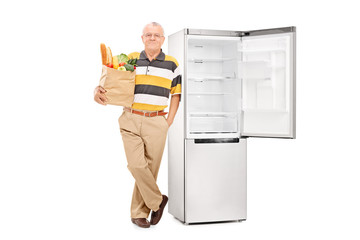 Senior holding a grocery bag by an empty fridge