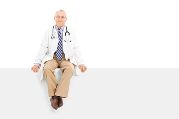 Mature doctor sitting on a blank panel