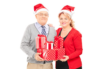 Mature couple posing with Christmas presents
