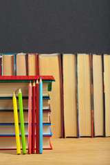 Pile of books and colored pencils on a wooden surface against th