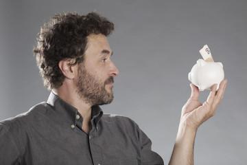 Mann hält Sparschwein in die Kamera, Nahaufnahme