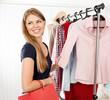 Pretty stylish female buyer choosing casual clothes in shop