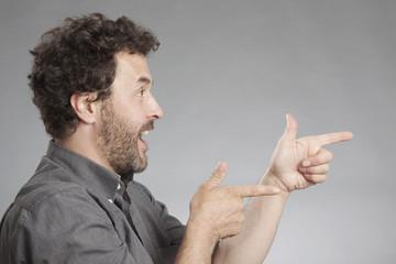 Mann in grauem Hemd zeigt mit dem Finger und lacht