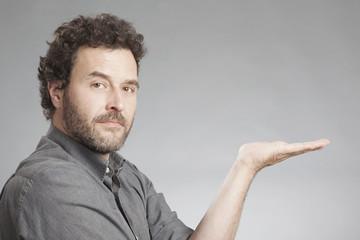 Mann in grauem Hemd hält die Handfläche nach oben