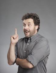 Mann in grauem Hemd zeigt nach oben
