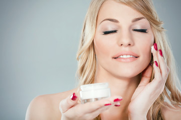Beautiful young woman applying moisturizer on her face