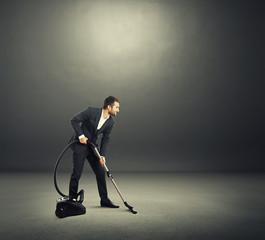 man in formal wear vacuuming dark room