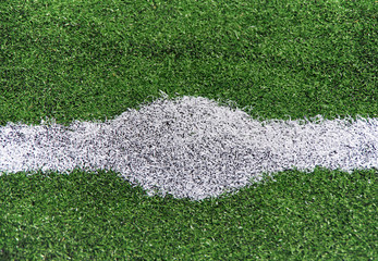 White abstract lines on a green football field.