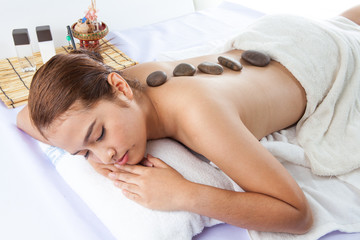 Massage Stones On Woman's Back At Spa