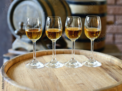 canvas print picture Glasses of wine in cellar with old barrels