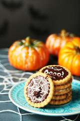 Tasty Halloween cookies on plate, on decorative spiderweb