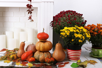 Pumpkins and flowers on brick wall and candles background