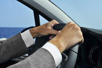 man in suit driving a car
