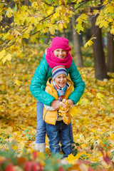 Cute kids with autumn leaves