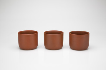three clay cups in a row, isolated on white background