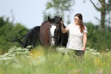 Frau mit Pferd auf Blumenwiese