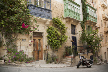 Motorbike on a Maltese street near a stone-made house