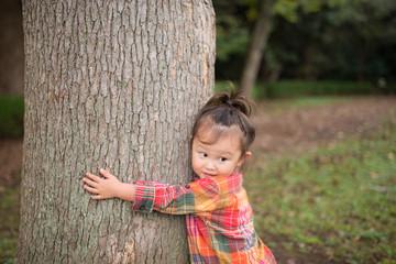 木に抱きつく少女
