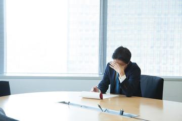 オフィスルームで顔を覆う男性