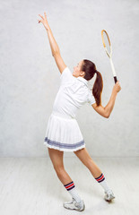 Beautiful girl in tennis clothes, brandishing a tennis racket on