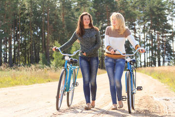 Two girls with bicycles in countryside