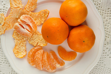 Fresh peeled and unpeeled oranges on a white plate
