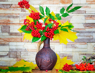Autumn still life: berries and autumn leaves in a ceramic vase.