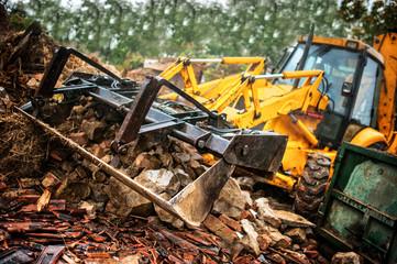 excavator loading demolition debris and concrete wasted walls