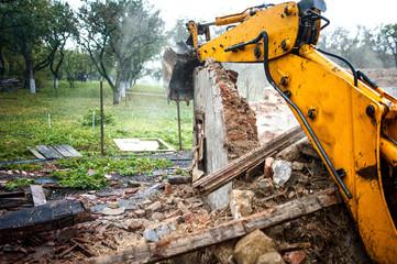Excavator demolishing a concrete wall