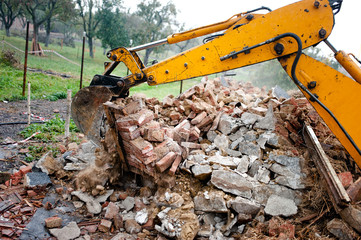 excavator on demolition site loading bricks and concrete walls
