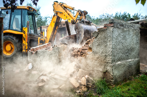 bulldozer demolishing concrete brick walls of small building - 71894542