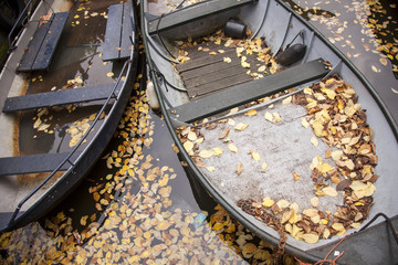 boats in canal full of fallen autumn leafs