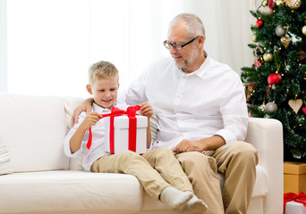 smiling grandfather and grandson with gift box