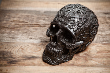Black skull on wooden table
