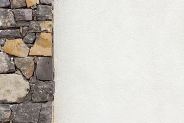 pilier de pierres naturelles et mur blanc crépi