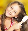 smiling little girl brushing her hair on a golden background