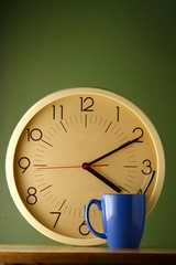 An analog clock and a blue coffee mug