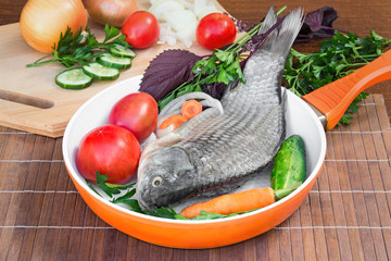 Fish and components for her preparation: vegetables, spices, par