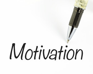 Pen writes motivation word on paper